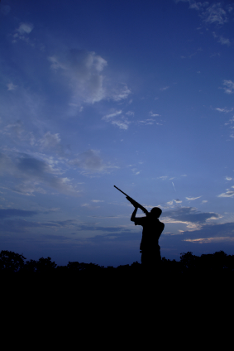 clay pigeon shooter silhouette at sunset